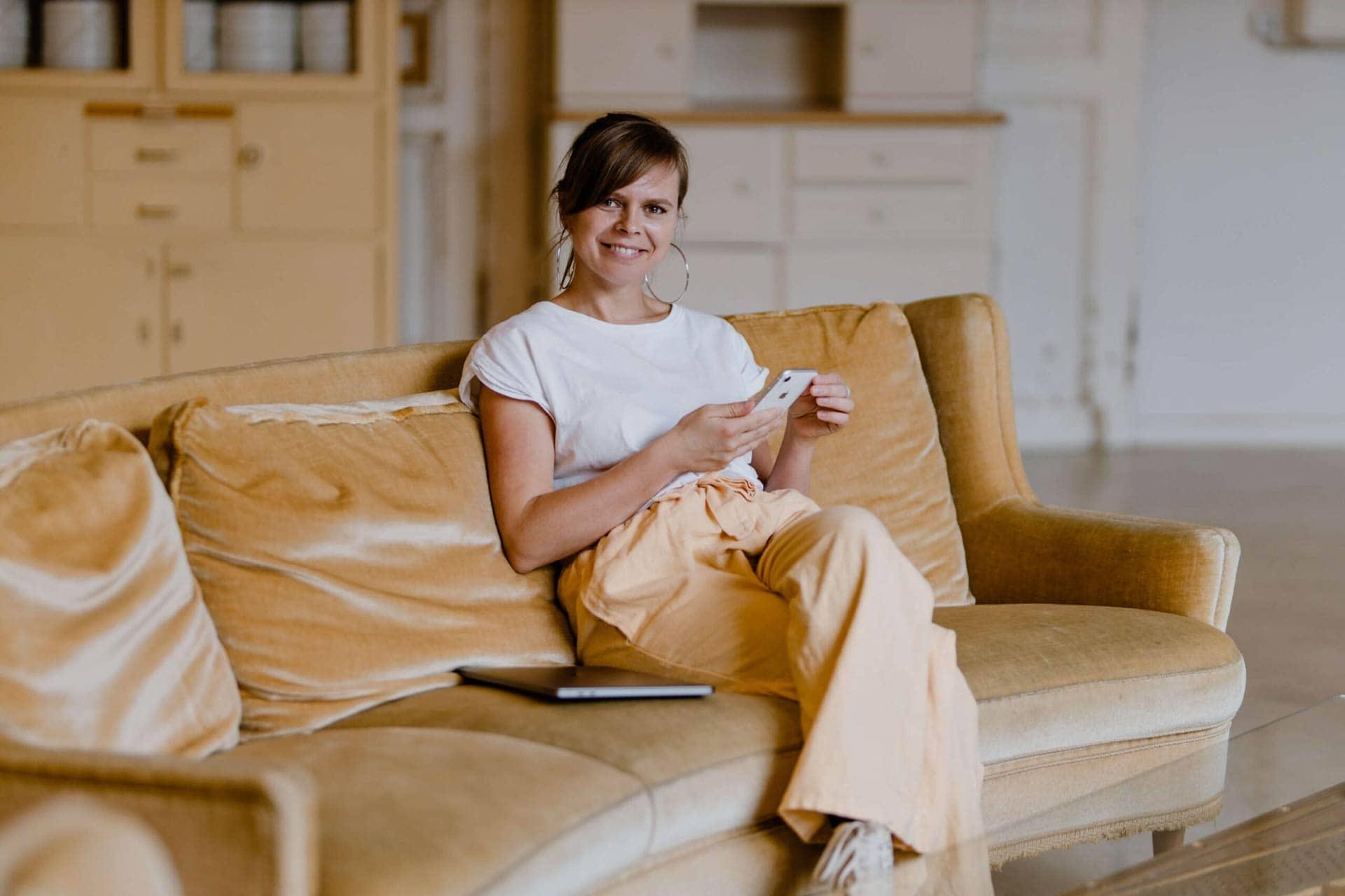 Anika Bors auf brauner Ledercouch sitzend