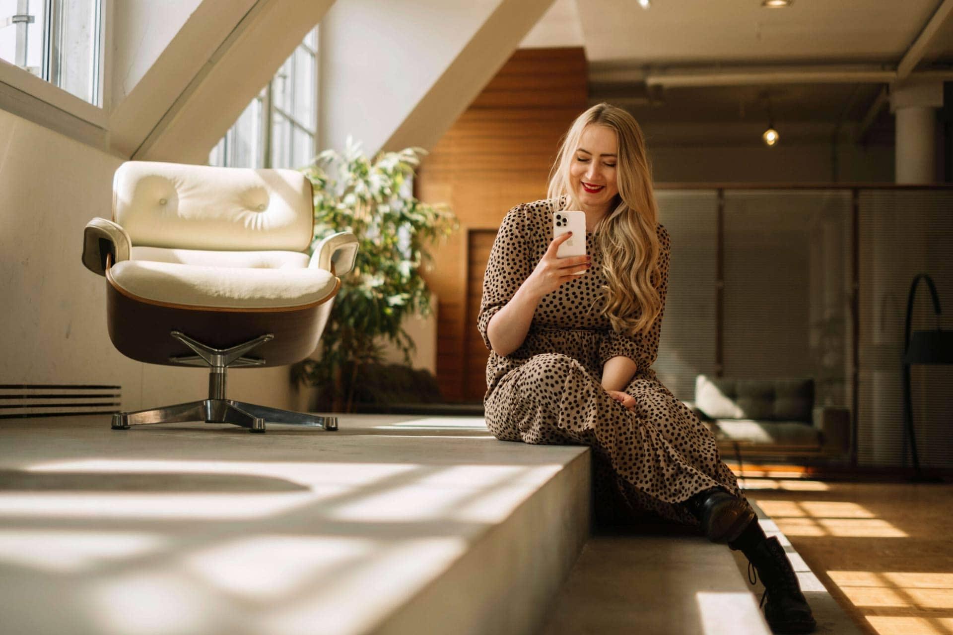 Jessica sitzt auf einer Treppe und schaut auf ihr Smartphone
