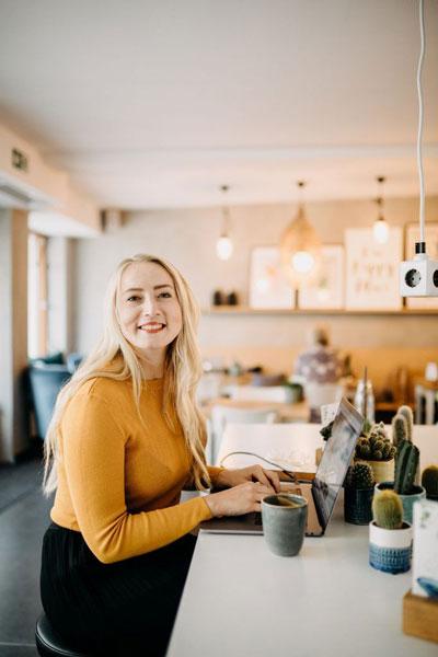 Jessica arbeitet im Cafe und lächelt seitlich in die Kamera