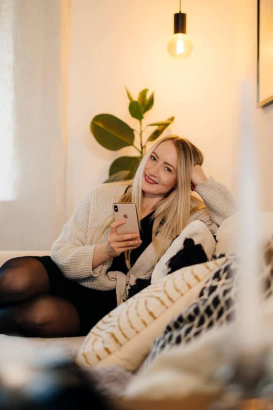 Jessica zu hause auf der Couch sitzend mit Smartphone