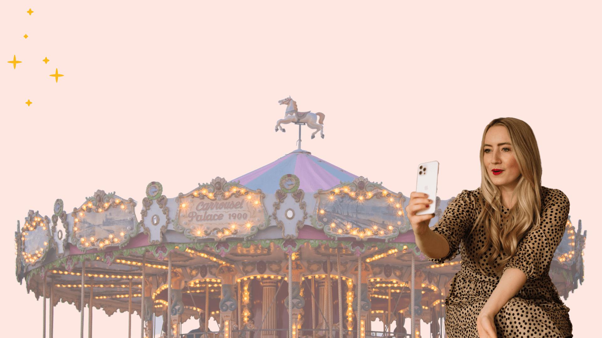 Großes Karussell vor rosafarbenem Hintergrund und Jessica, wie sie ihr in Handy guckt